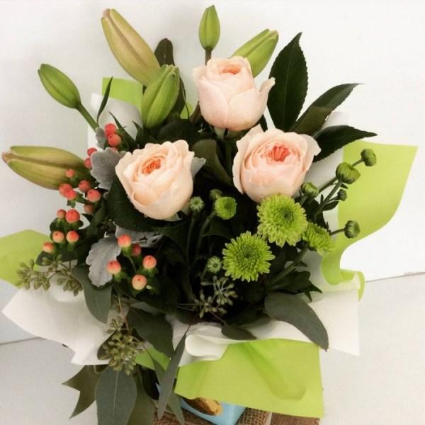 a simple box arrangement of seasonal flowers in pastel shades