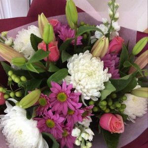 a soft hand tied bouquet of pastel flowers in pink and white.