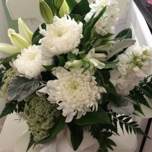 a simple white and green arrangement in a box