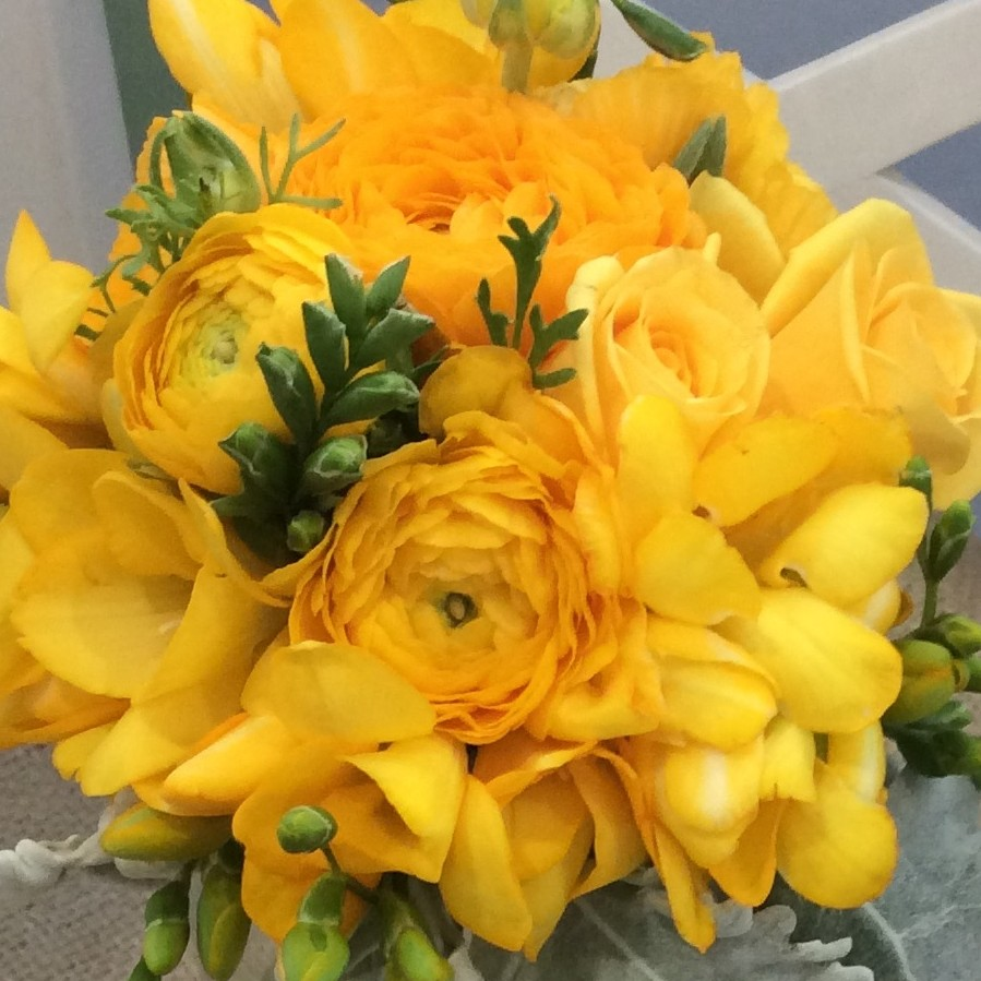 a compact posy style bouquet of seasonal yellow flowers