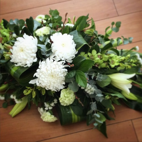 a full casket spray funeral tribute in white and green with rolled tropical leaves