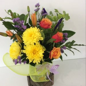 a glass cube vase arangement with brightly coloured seasonal flowers.