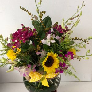 a glass fishbowl vase filled with yellow and purple seasonal flowers.