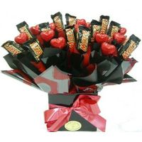 a chocolate bouquet in a black box with mars bars and red chocolate hearts wrapped in black and red.