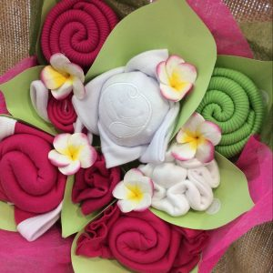 babybuds box heavensent in berry. pink white and green clothing items that are wrapped to look like flowers.