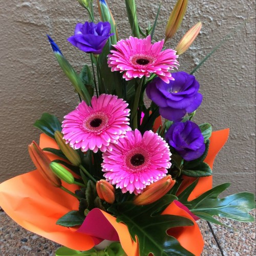 a front facing arrangement of seasonal flowers in hot pink, orange and purple.- A Touch of Class Florist