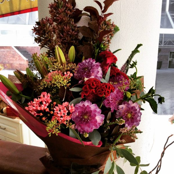 a large front facing bouquet of seasonal flowers in rich, warm tones.