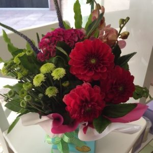 a posy box arrangement of pink, red and green flowers.