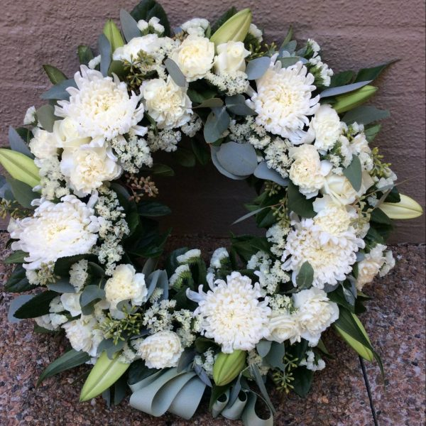 a large wreath made using white seasonal flowers with green foliage