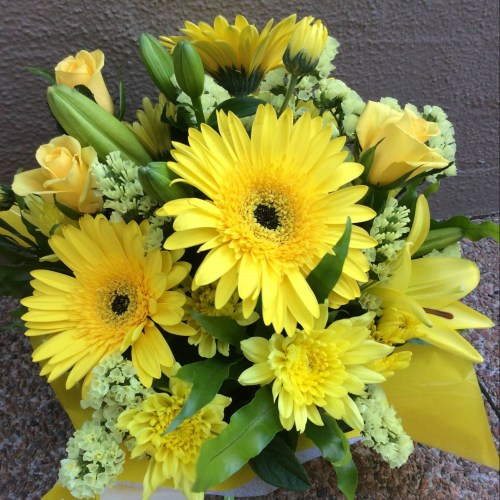 a box arrangement of yellow and cream flowers