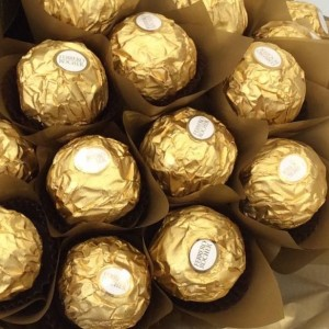 a chocolate bouquet made using 40 ferrero rocher chocolates wrapped in gold cellophane and a bottle of sparkling wine.