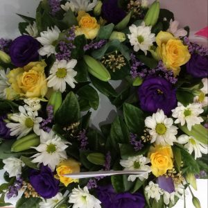 a medium sized wreath using yellow, purple and white flowers.