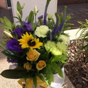 a box arrangement of yellow, purple and green seasonal flowers.