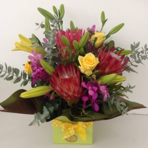 a box arrangement of bright seasonal flowers in red, pink and yellow