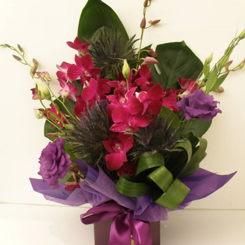 a simple box arrangement of orchids and other seasonal flowers in purple.