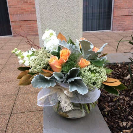 a fishbowl vase filled with peach, white and green seasonal flowers with grey foliage.
