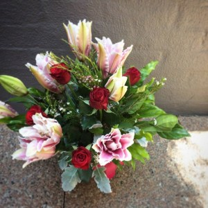 a box arrangement of pink oriental lilies and red roses.