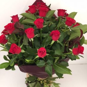 a long stem red rose hand tied bouquet. wrapped in burgundy with a green bow.