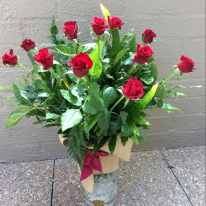 a glass vase filled with 12 long stem red roses.