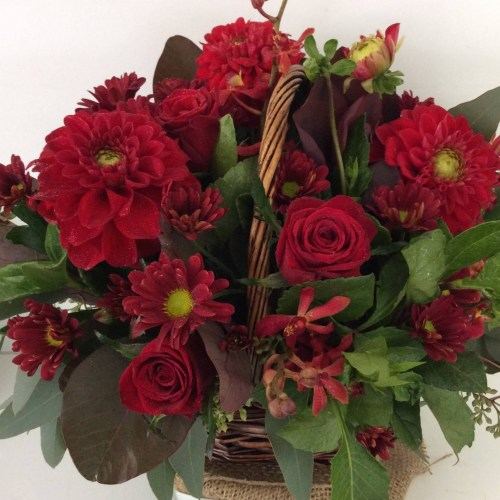 a wicker basket filled with red seasonal flowers.