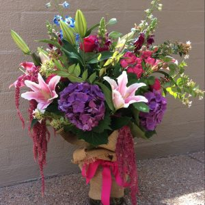 a large glass vase filled with colourful highly scented flowers.