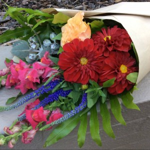 a seasonal wrap of bright flowers in red, pink and peach. wrapped in brown paper.