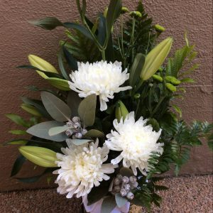 a seagrass basket filled with white and green flowers with silver foliage