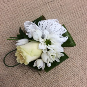 a white wrist corsage for a lady.