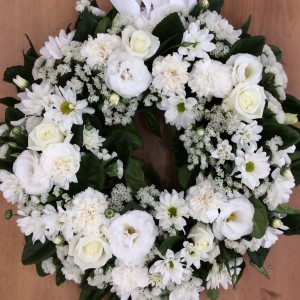 a small fresh flower wreath made using white flowers and green leaves