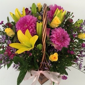 a wicker basket filled with yellow and pink seasonal flowers