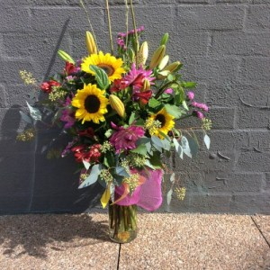 a large glass vase filled with yellow and pink flowers.