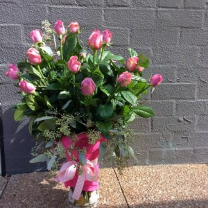a large glass vase filled with long stem pink roses and textural foliage.