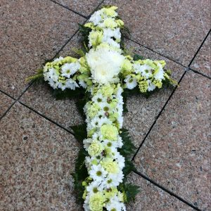 a white sympathy cross made using white and green seasonal flowers.