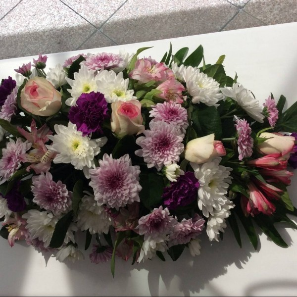 a teardrop shaped casket spray of seasonal flowers in pink, purple and white