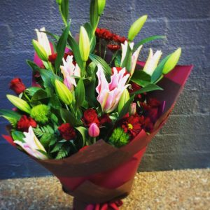 a large bouquet of pink oriental lilies, red roses and other seasonal flowers.
