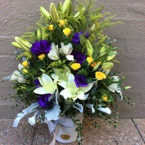 a traditional formal arrangement of white, yellow and purple seasonal flowers