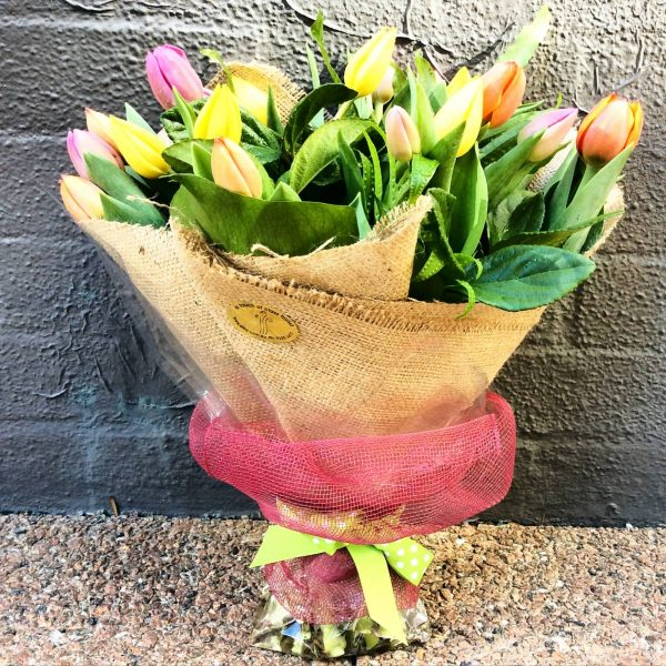a natural looking hand tied bouquet of mixed coloured tulips. wrapped in hessian and netting.