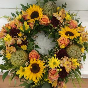 a wreath made using warm coloured fresh flowers. orange, yellow and gold.
