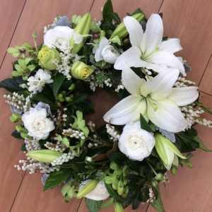 a wreath made using white flowers with open lilies as a feature.