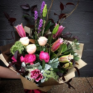 a vibrant front facing bouquet of lilies, liatris, peonies and roses in pink, purple and white.