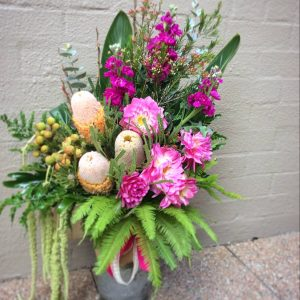 a clear glass vase filled with luscious foliages and seasonal flowers in pink, purple and orange.