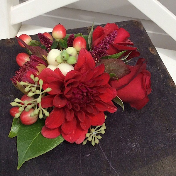 A beautiful wrist corsage in texural reds and a touch of white- A Touch of Class Florist