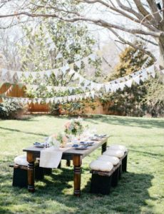 a rustic dining table layed for a party in a green garden with white bunting strung in the trees