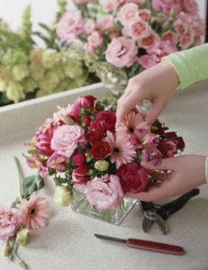 a florist arranging pink flowers into a formal arrangement.