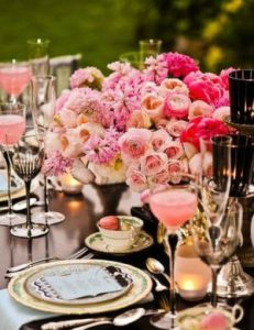a formal dining setting with pink flowers and gold touches.