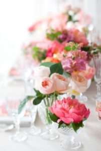 a close up of small vases containing stems of peonies and roses in pink and peach.