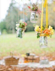 mason jars of yellow and orange flowers hanging above a table from yellow ribbon.