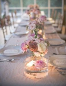 a soft and pretty table setting with candlelight casting a warm glow over the pink and white flowers.