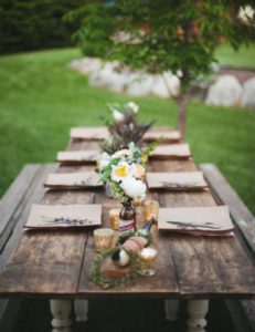 a rustic wooden dining table layed for a party with jars of flowers down the centre