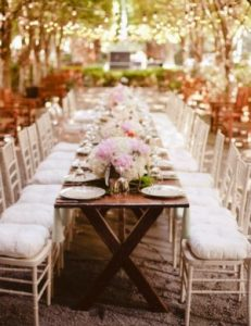 an elegant long wooden table layed for a formal event with pink and white floral arrangements down the centre.